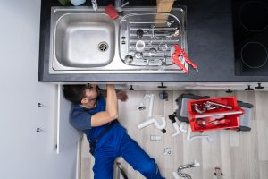Plumber fixing the pipe in the kitchen sink