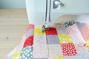 Quilting process: quilt and sewing machine on wooden desk