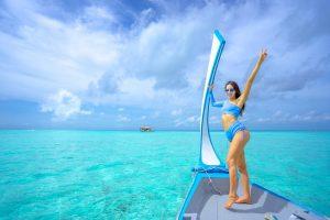 Woman wearing a blue colored high waisted thong bikini